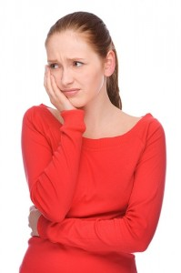 A woman with a tooth ache holds the side of her face.