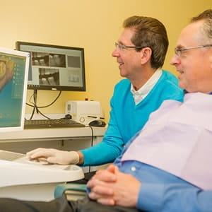 Dr. Silberman talking to a patient about his CEREC machine.