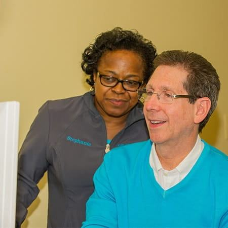 Dr. Silberman and his dental assistant looking at the CEREC technology