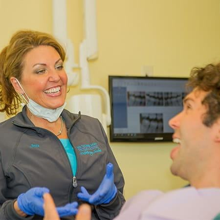 A dental hygienist at this Maryland dentist office joking with and explaining a procedure to a patient