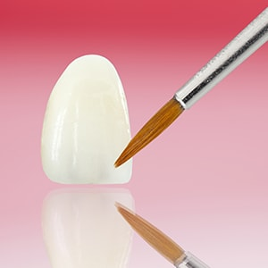 A porcelain veneer with a tiny paint brush in front of it to illustrate that we offer porcelain veneers as part of our restorative and cosmetic dentistry in Waldorf, MD