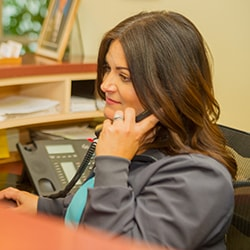 Sondra talking to a patient over the phone at our Waldorf, MD dentist office.