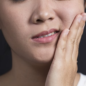 A woman with jaw pain from TMJ disorder