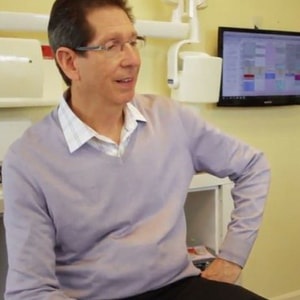 Dr. SIlberman, a Maryland dentist sitting in a chair listening to one of his patients