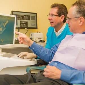 Dr. Silberman, a Maryland dentist, an an older patient reviewing a recommended dental procedure on a computer screen.