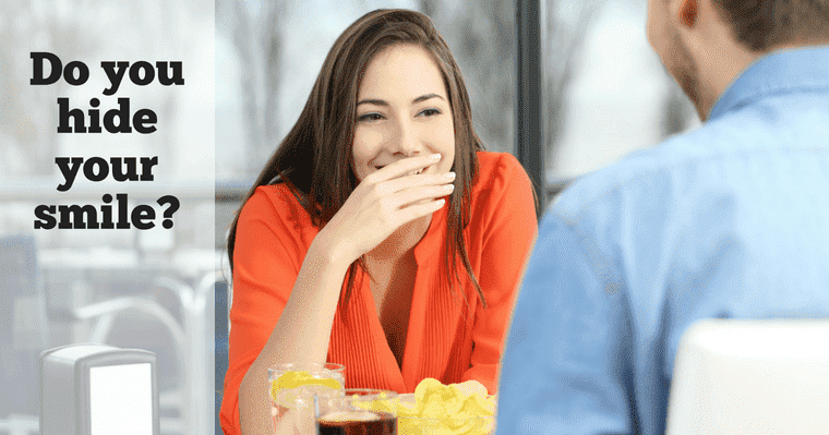 Woman on a date trying to hide her smile with her hand