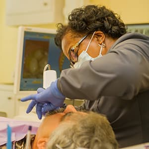 An assistant examining a patient's oral health