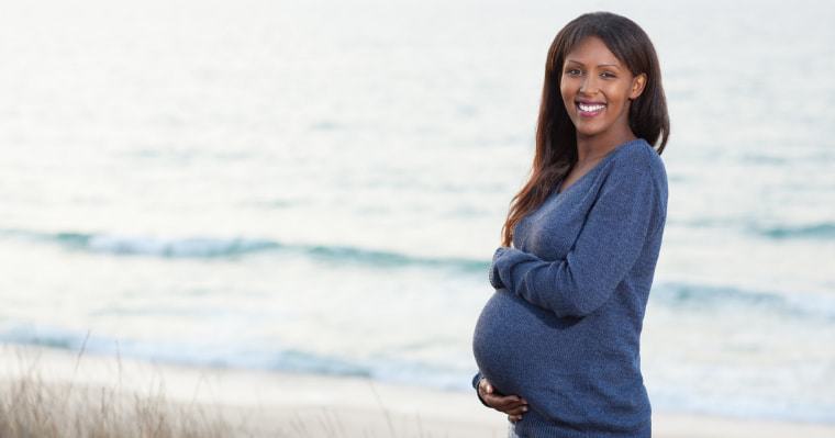 Pregnant woman smiling because she is well informed on her dental care during pregnancy
