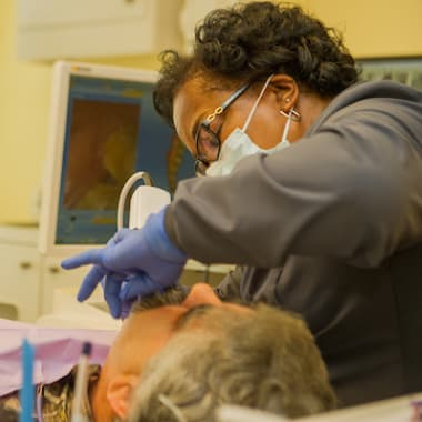A dental assistant providing treatment to a patient of Dr. Daniel Barakh
