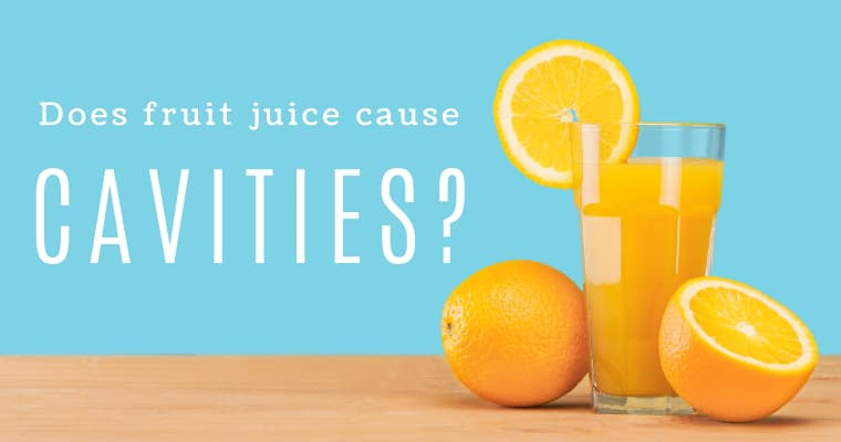 "A glass of orange juice with a slice of orange on top and two oranges beside it, on a blue background with the text ""Does fruit juice cause cavities?"""