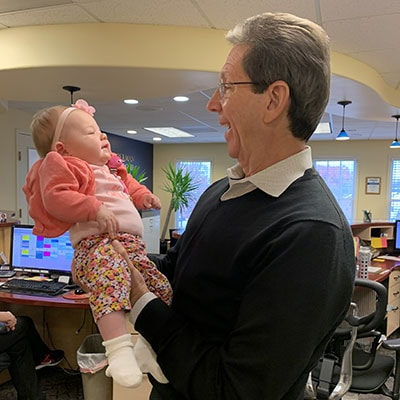 Dr. Silberman holding baby Olivia with a big smile