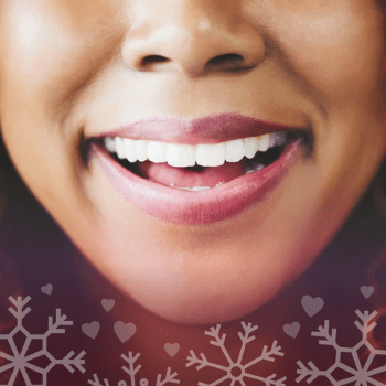 A close-up of a bright, white smile with snowflake and heart graphics around it