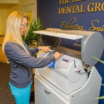 Dental Assistant, Kayla, giving an office tour showing our CEREC same-day crowns machine