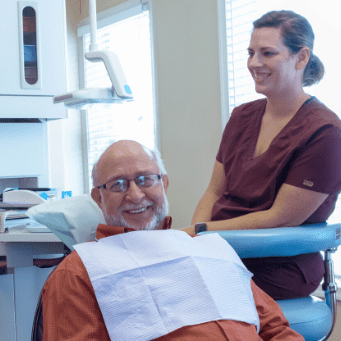 A patient and team member smiling about excellent dental care