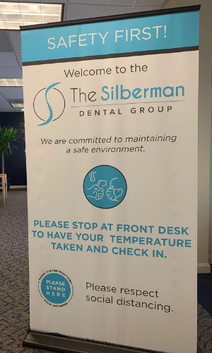 A sign in our office telling you to get temperature taken and check in.